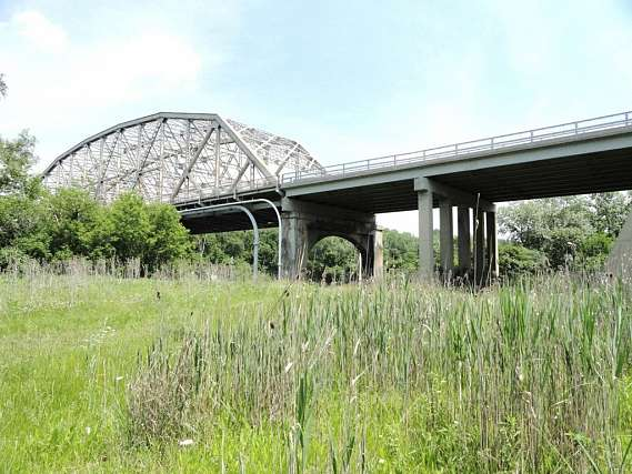A bridge supporting interstate 55 surrounded by a grassy area.